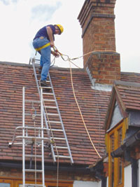 Engineer preparing to disconnect from ladder safety system to traverse chimney stack whilst attached to Chimney Strop via short cowstail webbing strop